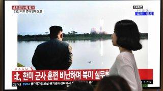 Fotografía de archivo de personas viendo el anuncio de lanzamiento en Corea del Norte.