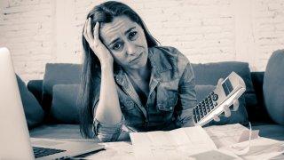 Foto en tono gris que muestra una madre soltera, sintiéndose estresada por sus finanzas mientras saca cuentas con la computadora portátil y una calculadora en la sala de estar.