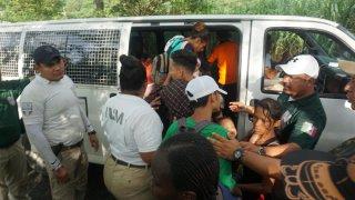 Grupo de personas migrantes rodeadas por agentes que los interceptaron.