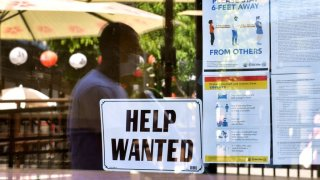 A 'Help Wanted' sign posted outside a restaurant.
