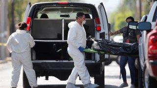 Tres peritos forenses, dos con trajes blancos, trasladan el cuerpo de una persona en una especie de camilla que bajaron de una camioneta negra.
